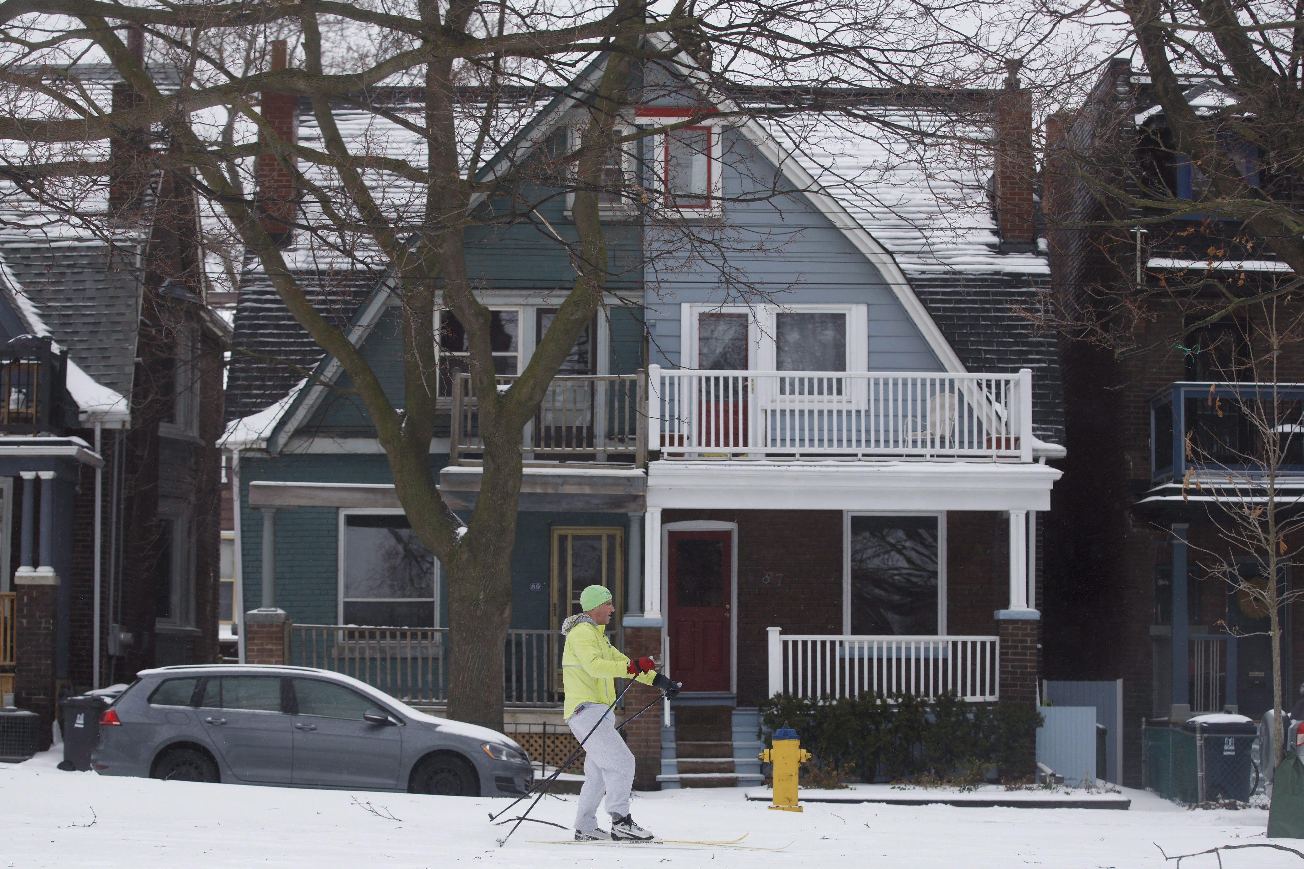 Man on skis in front of Toronto House.