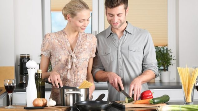 Couple in kitchen. Man cutting vegetables.