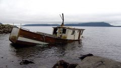 half sunk abandoned fishing boat.
