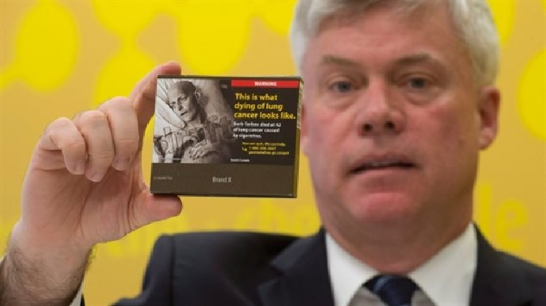 Rob Cunningham holds a package of cigarettes with a proposed plain packaging design..