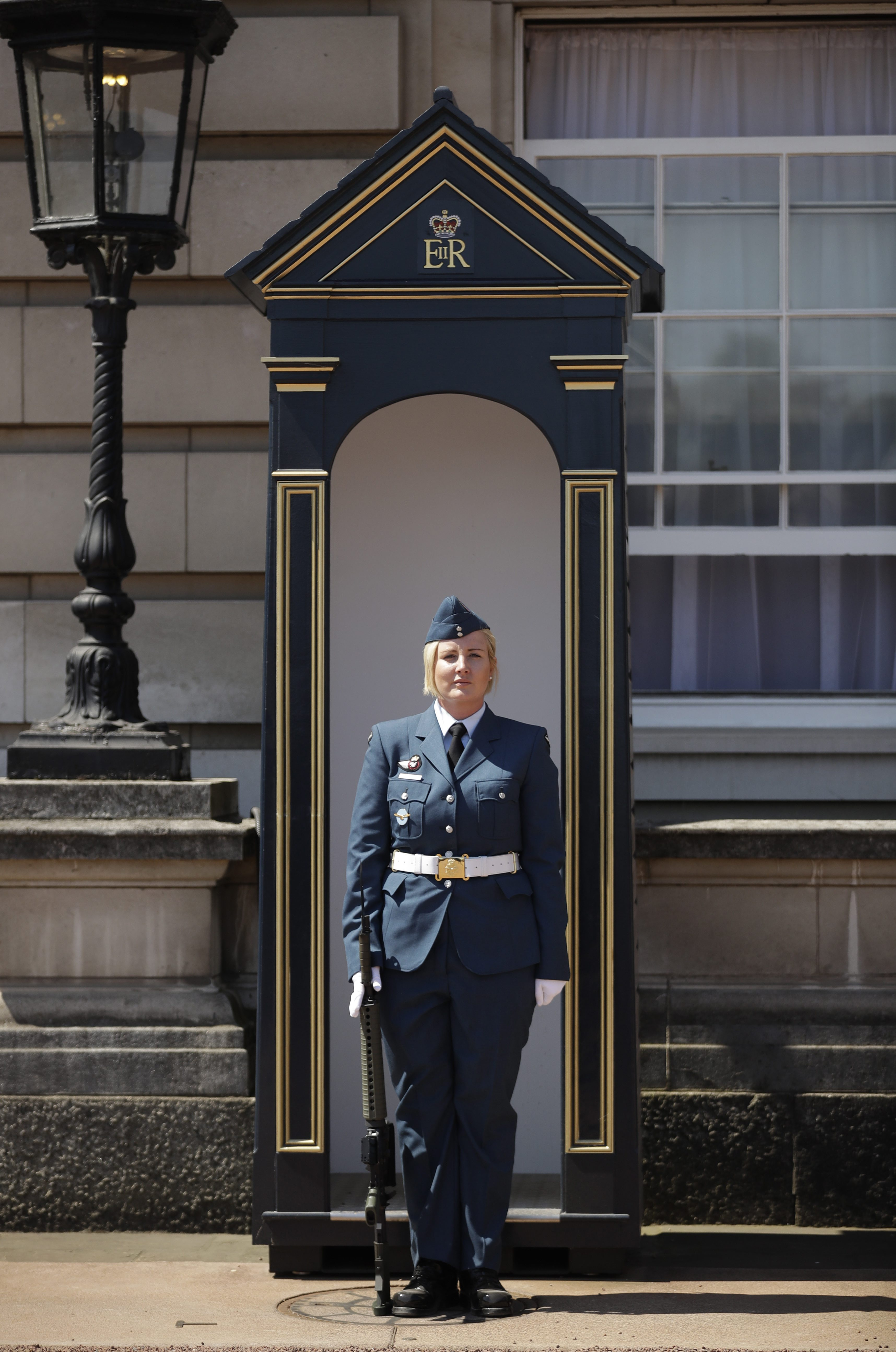 Female RCAF member in front of queen's guard post.