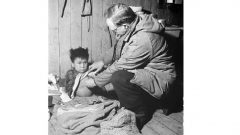 "Twice yearly, native settlements were visited by a government doctor. Shown here is T.J.Orford, doctor and agent for the James Bay district, with a child showing signs of tuberculosis. The child will be hospitalized ""outside""(ie in southern Canada) at government expense. Jan. 1946 (Library and ARchives Canada, Mikan-3225246)"