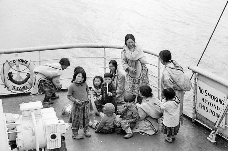 Indigenous people await medical examination aboard the Coast Guard Ship C.D. Howe at Coral Harbour, N.W.T. (now Coral Harbour/Salliq, Nunavut) in July, 1951. Throughout the 1950s and 60s, the Canadian Coast Guard ship made summer medical trips to the Eastern Arctic. If an infectious disease such as tuberculosis was found during the medicals, the infected individual was kept on board and not allowed to go ashore to collect belongings or say goodbye, before sailing south for treatment, which could take several years (National Film Board- Library and Archives Canada)