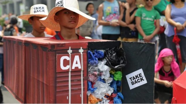 Filipino environmental activists wear a surprisingly realistic representation of a shipping container of garbage iner van filled with garbage to protest the cargo containers of garbage that were shipped from Canada to the Philippines in 2013 and 2014 (Aaron Favila/Associated Press)