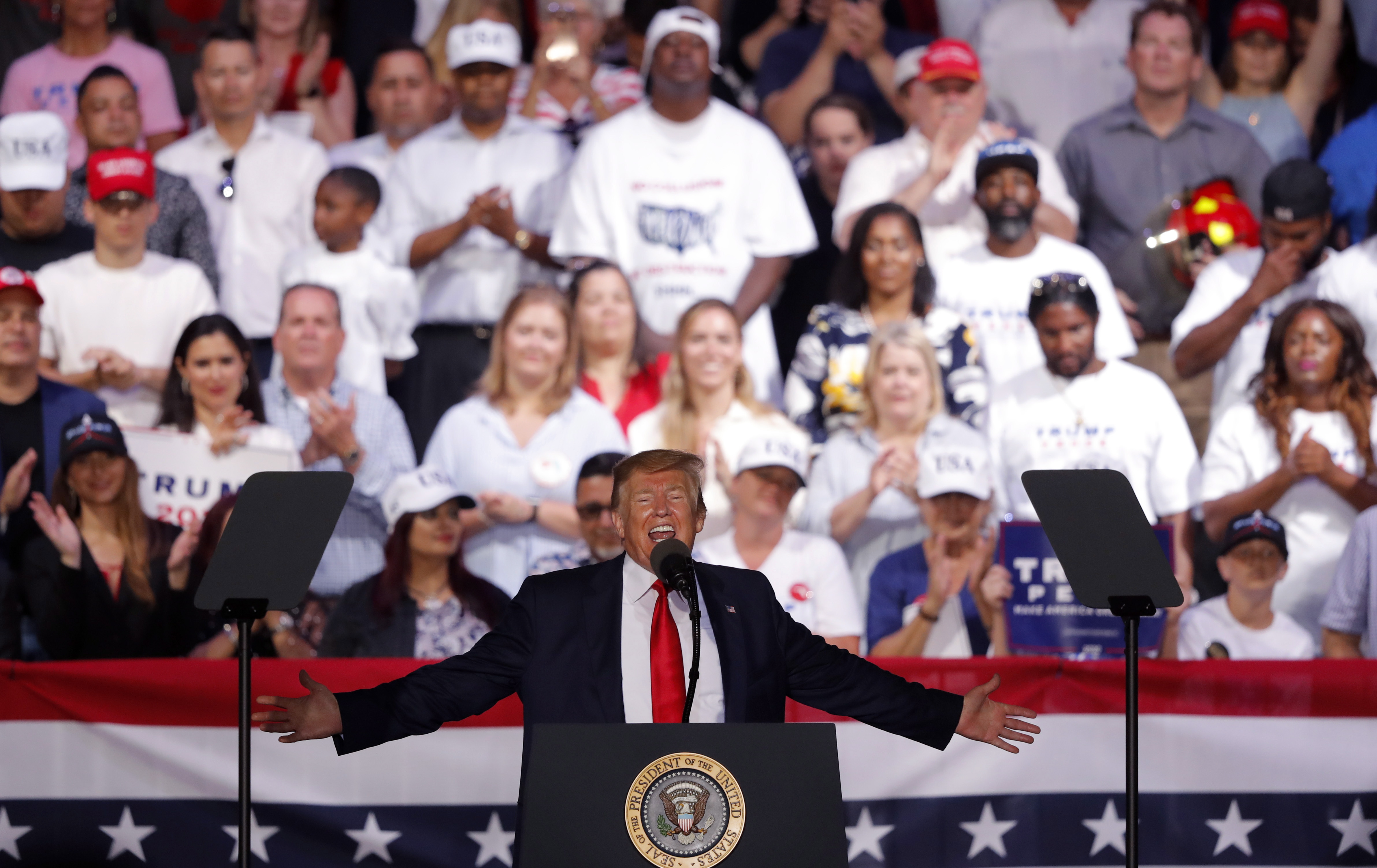 U.S. Pres. Donald Trump with arms outstretched addressing a rally.