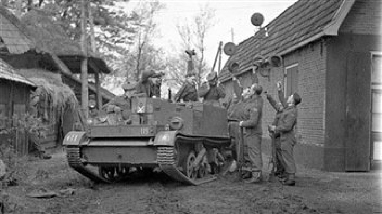 """Wireless operator Mac Keays relays the news of the end of hostilities to Universal Carrier driver Private Hugh McKerlain and infantrymen of """"D"""" Company, The Seaforth Highlanders of Canada, De Glindhorst, Netherlands, 5 May 1945 © archives Canada-MIKAN 3534474"""
