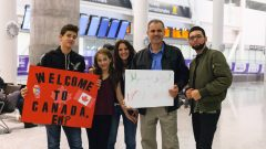 People at airport holding signs welcoming newcomers.
