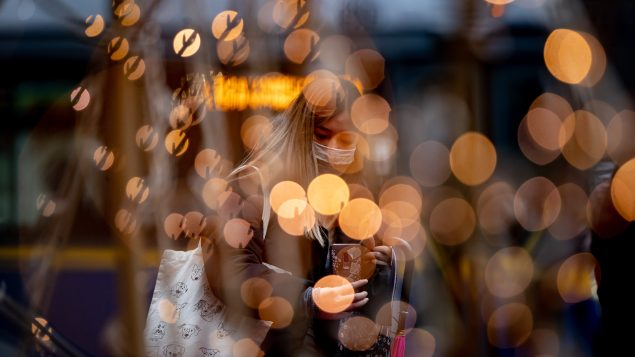 A woman wearing a face mask is framed by Christmas lights in downtown Vancouver