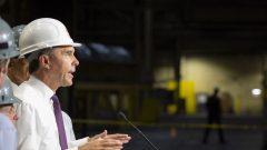 وزير المال الكندي بيل مورنو يرتدي خوذة بيضاء لدى زيارته أحد المصانع في هاميلتون في مقاطعة اونتاريو/Peter Power/CP