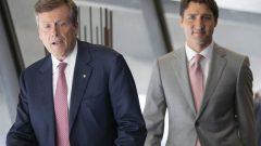 رئيس الحكومة جوستان ترودو (إلى اليمين) يدخل القصر البلدي في تورونتو إلى جانب العمدة جون توري/Chris Young/CP