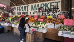 سيّدة تشتري الخضار في مدينة نيويورك وقد وضعت كمّامة طبيّة/Mark Lennihan/AP