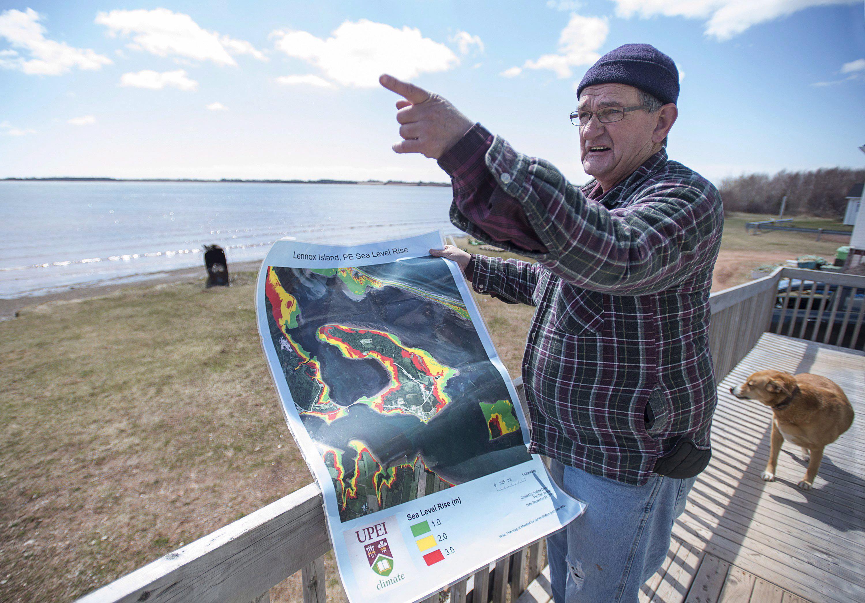 El residente de Lennox Island, Dave Haley, muestra un mapa del laboratorio de investigación climática de la Universidad de la Isla del Príncipe Eduardo, que muestra el aumento del nivel del mar en la isla. ©The Canadian Press/Andrew Vaughan