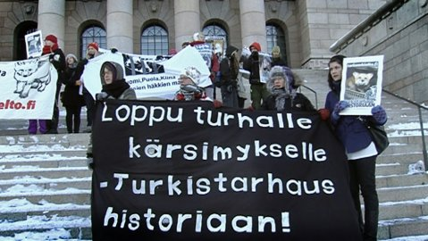 Protestors on the steps of Parliament in Helsinki. The banner reads,