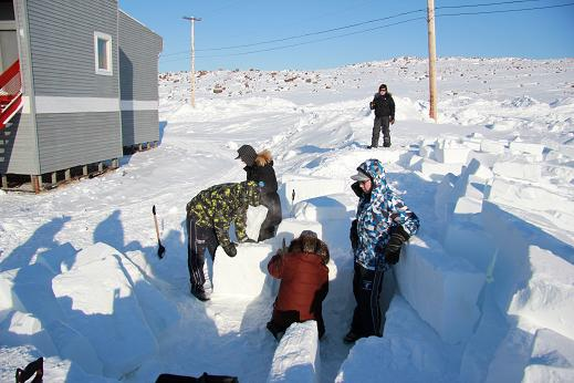 Making an igloo outside of Ulukhaktok's school. Usually the igloo is made out on the frozen harbour, but this year, the snow was not the right consistancy. Photo: Eilís Quinn, Radio Canada International.