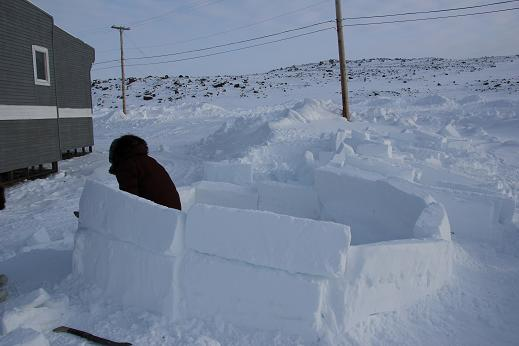 Ulukhaktok elder continues work on his annual igloo. The school principal had students come out to help the elder lift the heavy snow blocks. Photo: Eilís Quinn, Radio Canada International.