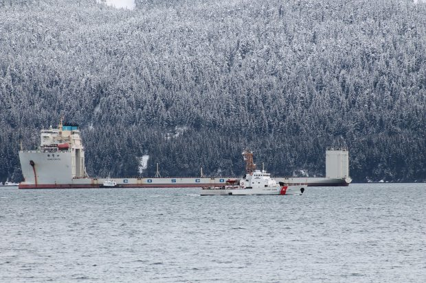 The 708-foot-long Xiang Yun Kou arrived in Seward, Alaska on Feb. 28, 2013, to dry-haul the Noble Discoverer to port in Asia. Pictured in the foreground is the Coast Guard cutter Mustang. Jackie Wilde photo. Alaska Dispatch.