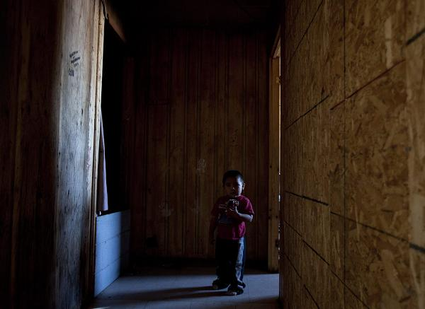 A young boy stands in the hallway of a house condemned due to structural and mold problems where four people live in Attawapiskat, Ont., Tuesday November 29, 2011. Adrian Wyld, The Canadian Press.