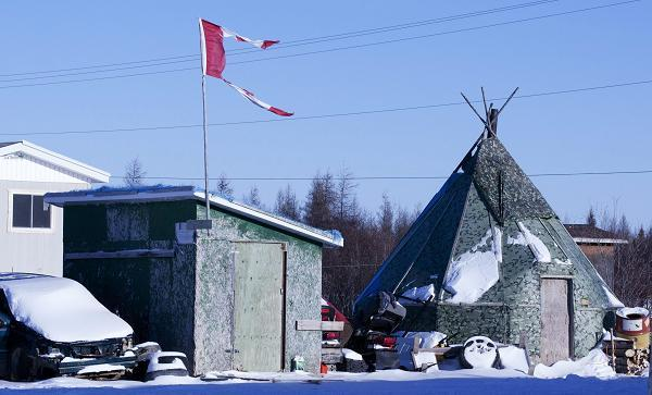 The remains of a Canadian flag can be seen flying over a building in Attawapiskat, Ont. Tuesday November 29, 2011. Adrian Wyld, The Canadian Press.