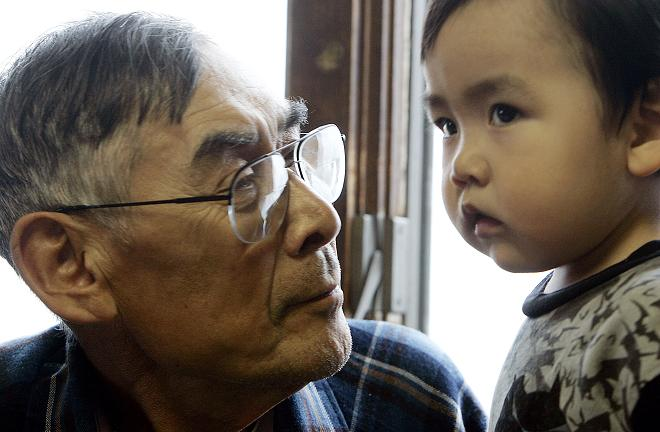 Johnny Weyiouamma Sr. looks at his grandson Keith in Shishmaref, Alaska. What will northern development mean for Arctic residents like them? AFP PHOTO/GABRIEL BOUYS