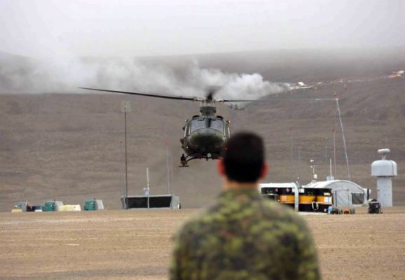 A Canadian solider observes a helicopter land near the downed 737. Department of National Defence, Master Cpl. Randy Burnside.