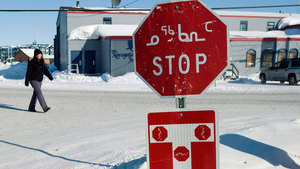 A person walks past a stop sign displayed in both English and Inuktitut in the Nunavut's capital, Iqaluit. (Nathan Denette/Canadian Press)