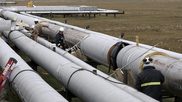 BP workers remove insulation from an oil transit pipeline at the Prudhoe Bay oil field on Alaska's North Slope Aug. 18, 2006 as other workers use ultrasound to test for weakness in the pipe due to corrosion. (Associated Press)