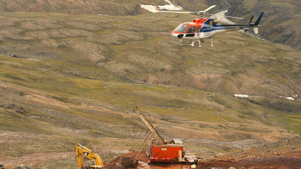 A helicopter passes over excavation equipment at the Mary River exploration camp. Photo: Vinnie Karetak, The Canadian Press