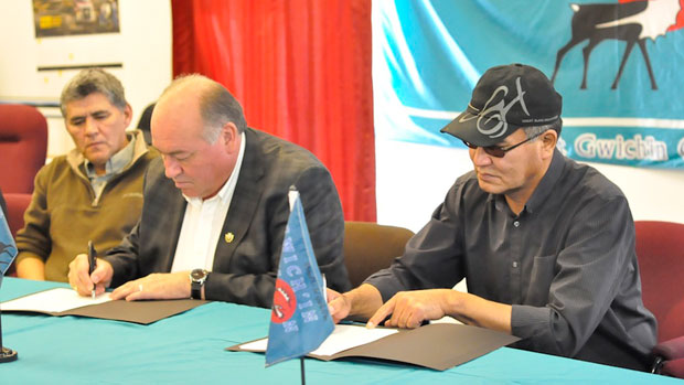 Minister Robert C. McLeod, who is also the MLA for Inuvik Twin Lakes, looks on as N.W.T. Premier Bob McLeod and Gwich'in Tribal Council president Robert Alexie Jr. sign the devolution Agreement in Principle in Aklavik, N.W.T., last week. (Philippe Morin/CBC)