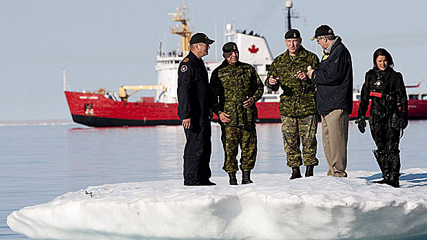 Prime Minister Stephen Harper, second from right, talks with Chief of the Defence Staff General Walter Natynczyk (centre) as they take part in a training exercise in Resolute, Nunavut on Aug. 25, 2010. The Canadian Coast Guard's medium icebreaker Henry Larsen is seen in Allen Bay. Canadian activity in the North, from searching for the Franklin expedition wreck to military manoeuvres, are about establishing sovereignty, experts say. (Sean Kilpatrick/Canadian Press)