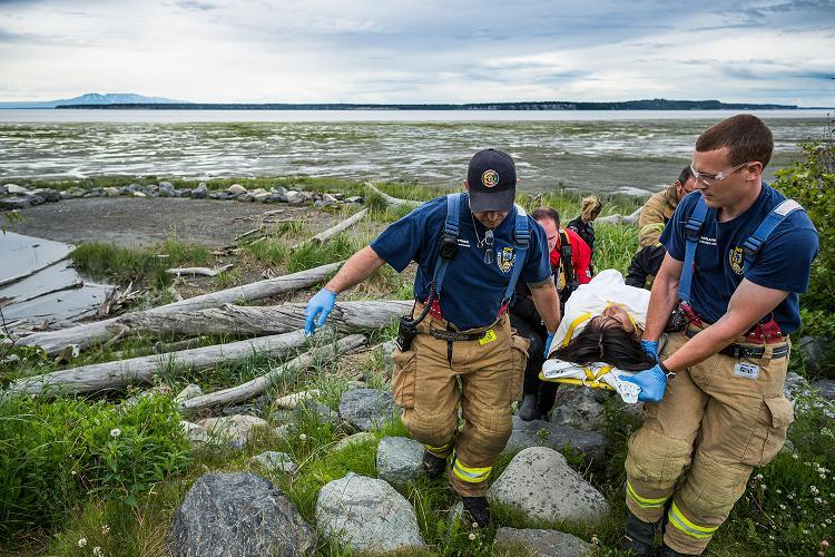 A man, barely responsive, is transported to an ambulance after he and his companion were rescued from the mudflats near downtown Anchorage. July 6, 2012. Photo: Loren Holmes. Alaska Dispatch.