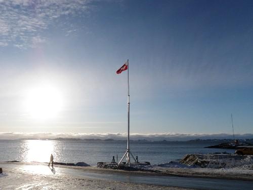Man walks past Greenlandic flag at sundown.