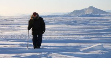 Inuit hunter and guide Elijah Pallituq walks on sea ice checking for seal breathing holes along the cracks in sea ice. Photo by Levon Sevunts.