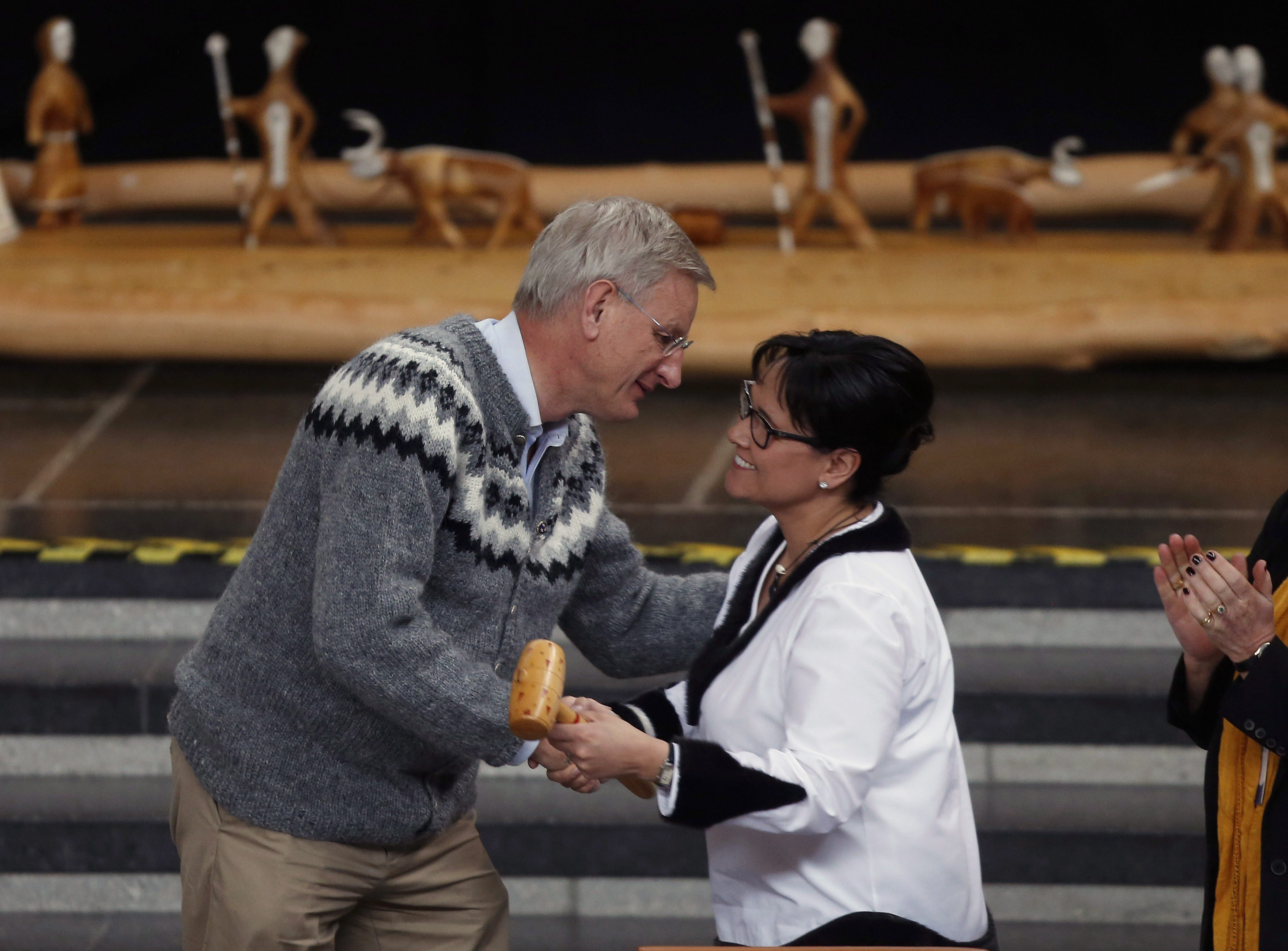 Sweden's Foreign Minister Carl Bildt hands the gavel which symbolizes handing the chairmanship of the Arctic Council to Canada's Minister of the Arctic Council Leona Aglukkaq, at the Arctic Council Ministerial Meeting, in Kiruna, Sweden, Wednesday, May 15, 2013, (Charles Dharapak / AP)