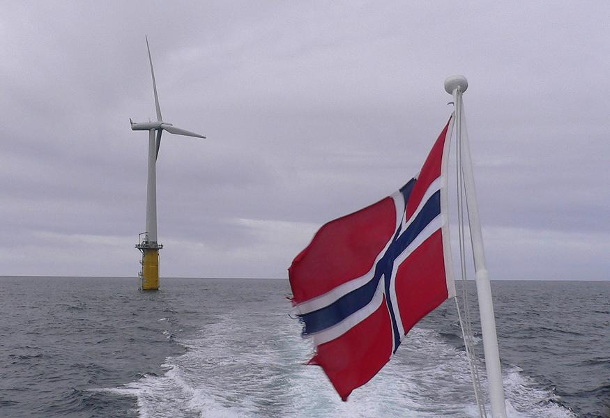 A Norwegian flag waving in front a statoil prototype floating wind turbine. (Igor Gedilaghine, AFP)
