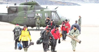 Some of the rescued hunters and tourists walk away from a military helicopter in Arctic Bay, Nunavut. (Photo courtesy of Niore Iqalukjuak)