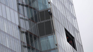 One of six Greenpeace protesters climbs up the Shard, the tallest building in western Europe, as workers look from a window during a protest against the oil company Shell's drilling in the Arctic. (Sang Tan/Associated Press)