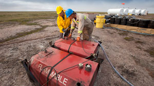 Two men work at the fuel storage site at the proposed Kiggavik uranium mine, near Baker Lake. (The Canadian Press)
