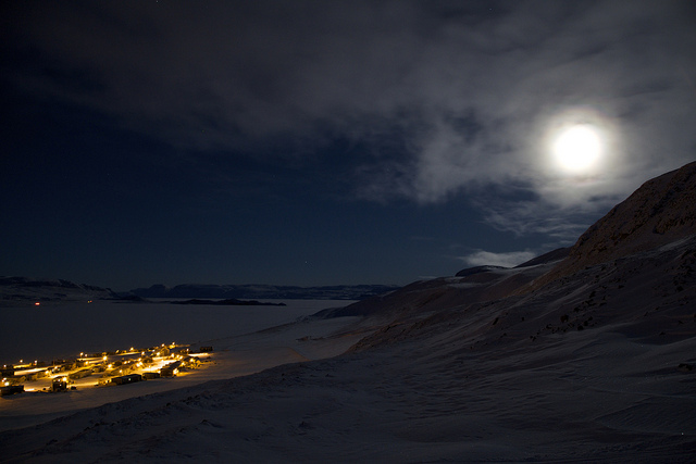 Part of Arctic Bay glows beneath the hills surrounding the community under the almost full moon.(Clare Kines)