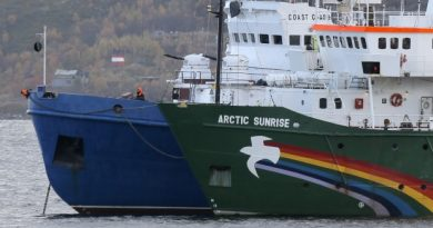 A crew member keeps watch aboard a Russian coast guard boat, left, as the Greenpeace ship 'Arctic Sunrise', right, is anchored next to it, in a small bay near Severomorsk, Russia. (The Associated Press)