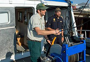 Parks Canada underwater archeologist Ryan Harris, left, and Petty Officer 2nd Class Yves Bernard of the Royal Canadian Navy fit a winch aboard the Martin Bergmann in Cambridge Bay, Nunavut, during final preparations for this year's Franklin search. (Parks Canada)