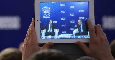 A man takes a photo of Russian President Vladimir Putin, right, and Prime Minister Dmitry Medvedev, with a tablet in 2013. (AP Photo/RIA-Novosti, Alexander Astafyev, Government Press Service)