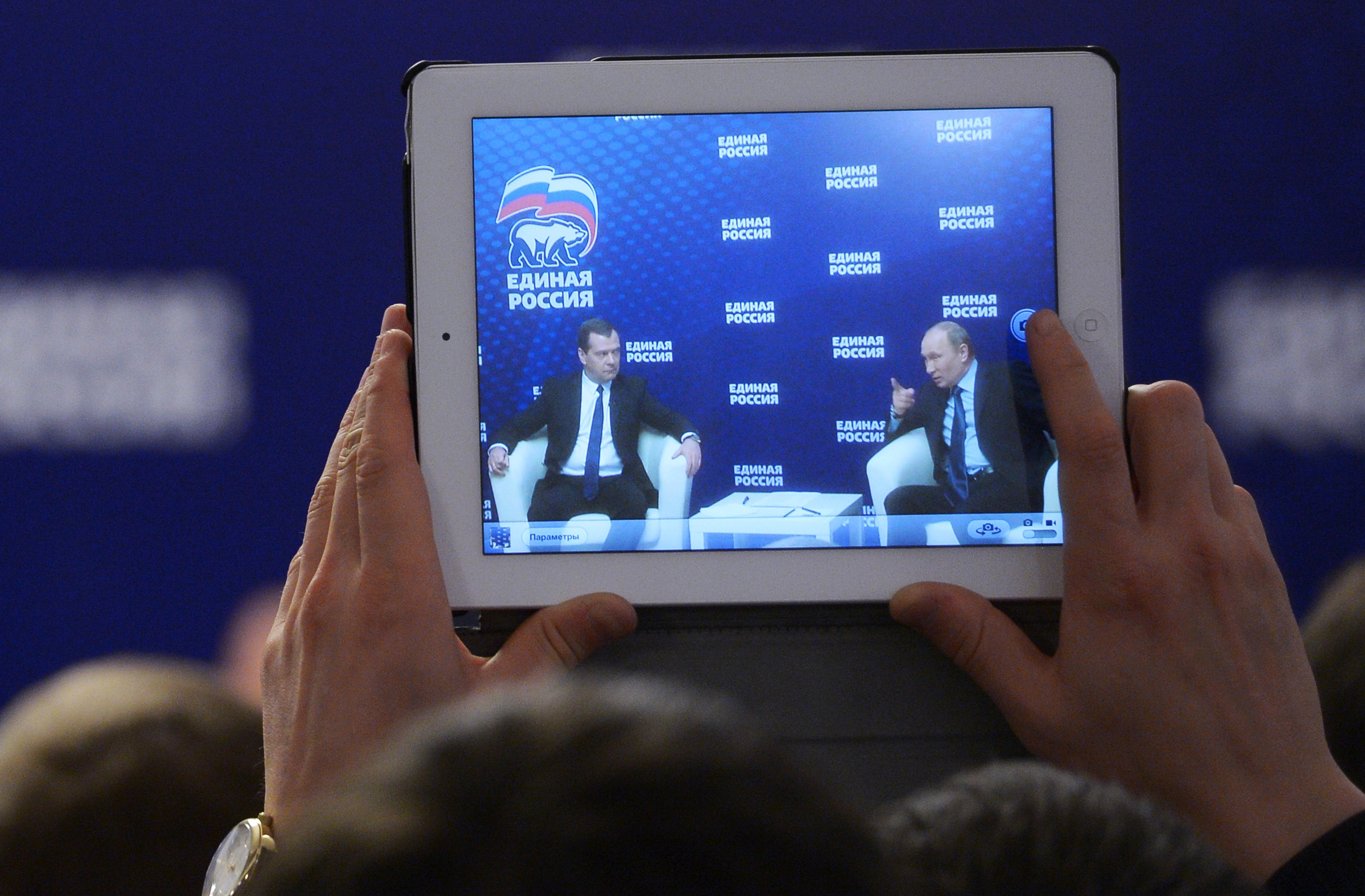 A man takes a photo of Russian President Vladimir Putin, right, and Prime Minister Dmitry Medvedev, with a tablet in 2013. (AP Photo/RIA-Novosti, Alexander Astafyev, Government Press Service)
