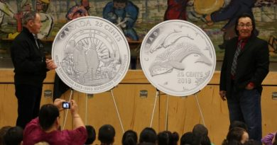 Royal Canadian Mint Board of Directors member Claude Bennett and Cape Dorset artist Tim Pitsiulak unveil new 25-cent coins celebrating the 100th anniversary of the Canadian Arctic Expedition and Life in the North at Kullik Illihakvik Elementary school in Cambridge Bay. (Royal Canadian Mint)