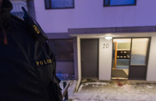 A police officer stands guard at a house where a man was shot dead by poilce in Reykjaiík on December 2, 2013. (Halldor Kolbeins / AFP)