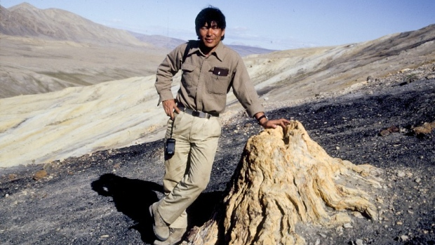 Dr. Tatsuo Sweda, then of Nagoya University, Japan, poses with a fossilized stump found near Strathcona Fiord on Nunavut's Ellesmere Island in 1990. The region has been hailed as 'a paleobiological hotspot.' (Courtesy Jim Basinger)