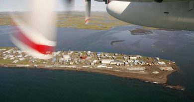 A Coast Guard C-130 flys past a coastal village on the Chukchi Sea near Kotzebue, Alaska. (Al Grillo / AP)