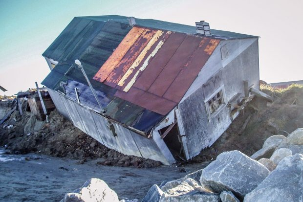 A home in Shishmaref falls into the sea. Shishmaref is highly susceptible to coastal erosion. (Courtesy Tony Weyiouanna / Alaska Dispatch)