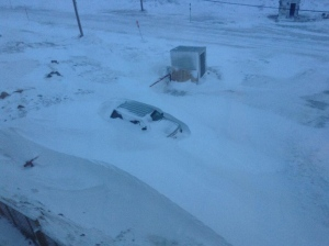 A car buried in a snowdrift. Winds were still raging when people in Iqaluit woke up Wednesday morning, expecting to find damage. (Kenny Bell)