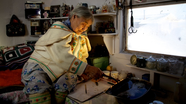 Qapik Attagutsiak of Arctic Bay, Nunavut, lights a qulliq — a traditional oil lamp — in her home. (Courtesy Clare Kines)