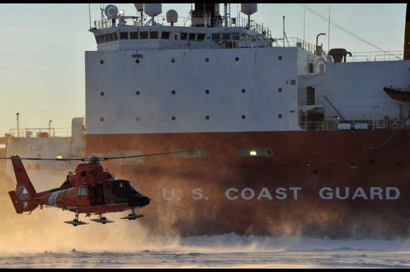 A Coast Guard helicopter crew lands on frozen sea ice in front of the Coast Guard Cutter Healy outside the Port of Nome on Jan. 18, 2012. (U.S. Coast Guard)